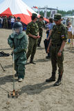 Los visitantes de la demostración intentan encendido el traje del bombero Foto de archivo libre de regalías