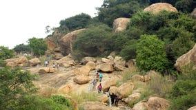 Los visitantes en la manera del paso de camas de piedra jain en el complejo sittanavasal del templo de la cueva Fotos de archivo