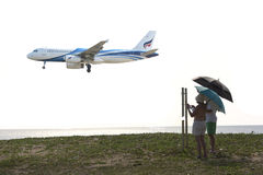 Los visitantes interesados como el avión aterrizaban en el aeropuerto Imágenes de archivo libres de regalías