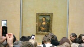 Los visitantes toman las fotos de Mona Lisa (Leonardo DaVinci), el museo del Louvre, metrajes
