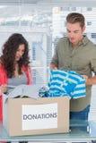 Los voluntarios serios que sacan visten de una caja de la donación Imagenes de archivo
