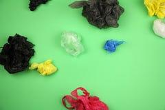 Los von zerknittert benutzte farbige Plastiktaschen auf grünem Hintergrund, großes ökologisches Problem stockbilder