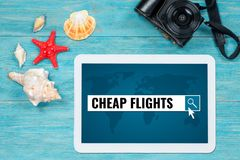 Los vuelos baratos que buscaban, página del sitio web se abrieron en la tableta digital l foto de archivo libre de regalías