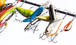 Los wobblers coloreados del cebo de pesca se suspendan en espacio en blanco del ` s de la barra Fotos de archivo