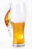 Los wobblers del cebo de pesca acercan al vidrio con la cerveza Imágenes de archivo libres de regalías