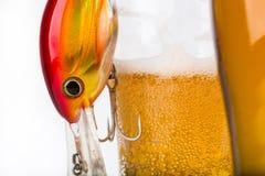 Los wobblers del cebo de pesca acercan al vidrio con la cerveza Foto de archivo