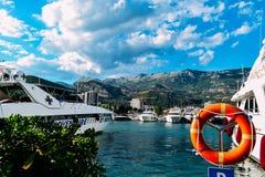 Los yates se colocan en el embarcadero en el puerto en el fondo de las montañas balcánicas en un día de verano Fotografía de archivo libre de regalías