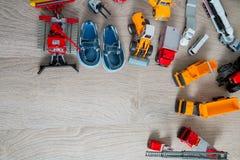 Los zapatos azules del barco para el muchacho cerca fijaron del juguete del coche en fondo de madera gris Visión superior Capítul Imagen de archivo libre de regalías