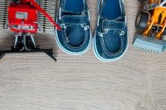 Los zapatos azules del barco para el muchacho cerca fijaron del juguete del coche en fondo de madera gris Visión superior Capítul Fotos de archivo