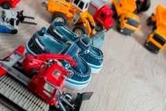 Los zapatos azules del barco para el muchacho cerca fijaron del juguete del coche en fondo de madera gris Visión superior Capítul Foto de archivo libre de regalías