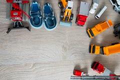 Los zapatos azules del barco para el muchacho cerca fijaron del juguete del coche Visión superior Capítulo Copie el espacio Fotos de archivo libres de regalías