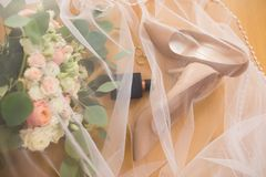Los zapatos beige de los bride's y otros accesorios se cubren el velo Accesorios de la boda: zapatos, anillos, perfume, ramo Fotografía de archivo