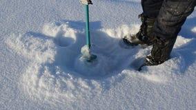Los zapatos calientes del pescador perforan la afición de la temporada de pesca de la herramienta del hielo del icehole almacen de metraje de vídeo