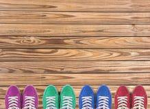 Los zapatos coloridos fijaron en fondo de madera con el espacio de la copia Visión superior imagenes de archivo