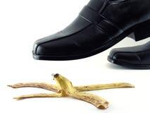 Los zapatos de cuero negros están pisando una cáscara del plátano en el fondo blanco Imagenes de archivo