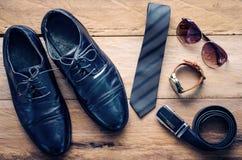 Los zapatos de cuero y los accesorios para el trabajo mintieron en el piso de madera Imagen de archivo libre de regalías