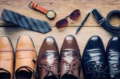 Los zapatos de cuero y los accesorios para el trabajo mintieron en el piso de madera Imágenes de archivo libres de regalías