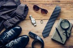 Los zapatos de cuero y los accesorios para el trabajo mintieron en el piso de madera Foto de archivo