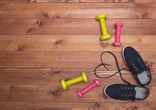 Los zapatos de la aptitud con el corazón atan, los pesos en fondo de madera Imagen de archivo
