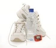 Los zapatos de la aptitud con el podómetro y agua revisaron 2 fotografía de archivo