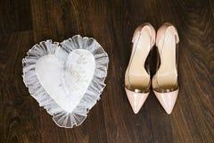 Los zapatos de la boda beige y los anillos de bodas nupciales del oro en blanco adornan la almohada Fotos de archivo libres de regalías