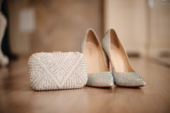 Los zapatos de la novia con los guijarros brillantes se colocan al lado de un embrague blanco Fotografía de archivo