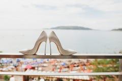 Los zapatos de la novia de la boda con la opinión del mar Imagenes de archivo