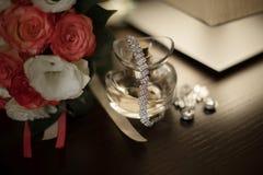 Los zapatos de las mujeres, perfumes, tarjetas de la invitación, anillos de bodas en un fondo aislado para la novia foto de archivo