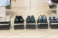Los zapatos de los hombres en las cajas negras imagen de archivo