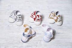 los zapatos de los niños multicolores en un fondo de madera no uniforme blanco-gris imagen de archivo
