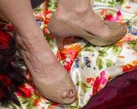 Los zapatos de oro del tacón alto dieron vuelta a casi 90 grados en los tobillos Fotografía de archivo libre de regalías