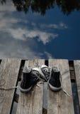 Los zapatos del adolescente negro que se colocan en el puente afilan, concepto bien escogido Imagen de archivo