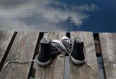 Los zapatos del adolescente negro que se colocan en el puente afilan, concepto bien escogido Fotografía de archivo