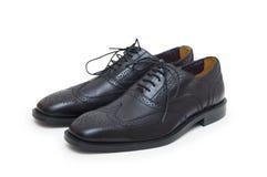 Los zapatos del hombre negro en el fondo blanco. Imagenes de archivo