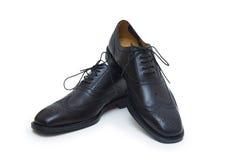 Los zapatos del hombre negro en el fondo blanco. Imagen de archivo
