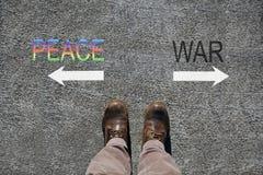 Los zapatos del hombre ven desde arriba, paz de las palabras y guerra y dos flechas que indican las direcciones con el espacio de imagen de archivo