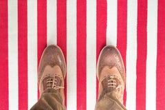Los zapatos del negocio en un blanco rojo rayaron carped Foto de archivo