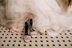 Los zapatos elegantes rosados de las sandalias del ` s de la novia en el piso al lado de los pies y de una boda tratan el vestido Imagen de archivo
