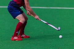 Los zapatos rojos del jugador de hockey pegan la bola Fotos de archivo