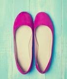 Los zapatos rosados de la mujer en azul colorearon el fondo de madera Foto de archivo