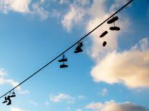 Los zapatos siluetean el colgante en un cable con el fondo del cielo azul imagenes de archivo