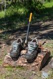 Los zapatos turísticos se secan en la clave que el hacha se pega, Altai, Rusia imagen de archivo