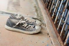 los zapatos viejos delante del metal cortan la puerta y cemen sucios Imagen de archivo libre de regalías