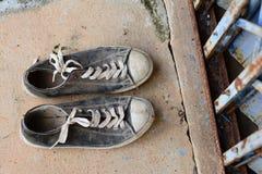 los zapatos viejos delante del metal cortan la puerta y cemen sucios Fotografía de archivo libre de regalías