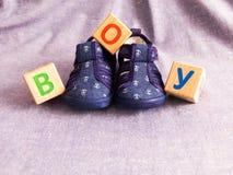 Los zapatos y los cubos de madera de los niños fotografía de archivo