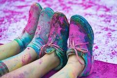 Los zapatos y las piernas coloridos de adolescentes con el polvo púrpura del color en el evento público el funcionamiento del col Imágenes de archivo libres de regalías