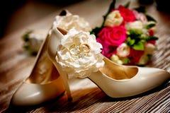 Los zapatos y los anillos nupciales contra ramo de la boda florecen Fotos de archivo libres de regalías
