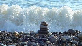Los ZENES Stone apilan en la playa con resaca del mar detrás metrajes