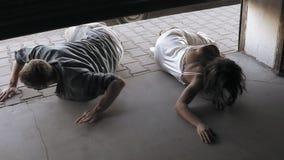 Los zombis femeninos y masculinos están persiguiendo a la muchacha en la calle Chica joven que corre en asustadizo y que oculta e almacen de video