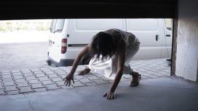 Los zombis femeninos y masculinos están persiguiendo a la muchacha en la calle Chica joven que corre en asustadizo y que oculta e metrajes